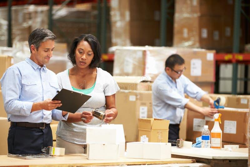 Работники в складе подготавливая товары для отправки стоковая фотография
