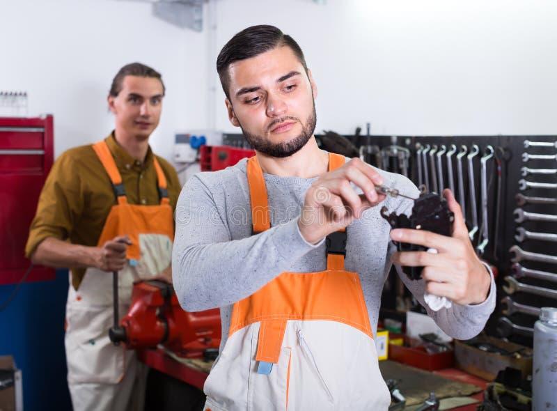 Работники в форме на мастерской стоковое изображение