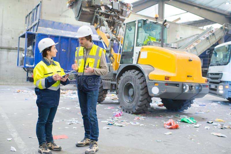 Работники говоря на месте выжимк стоковая фотография