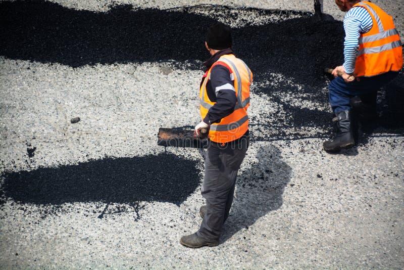 Работники дороги ремонтируя раздел дороги асфальта стоковое изображение rf