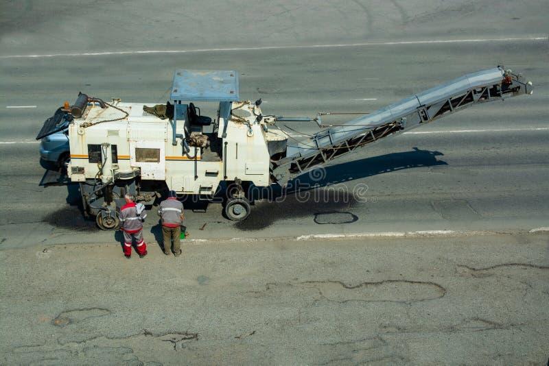 Работники дороги стоят около филировальной машины дороги стоковая фотография rf