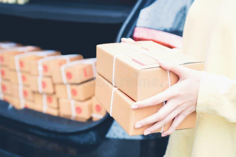 Работники держат пакет в автомобиле для посылки к клиенту Заказывание на линии для удобства клиентов стоковые фотографии rf