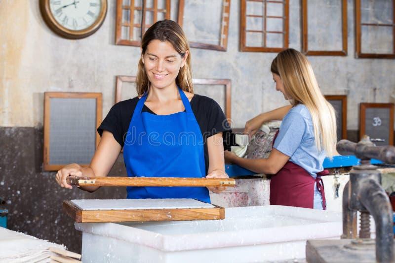 Работники делая бумаги в фабрике стоковое фото