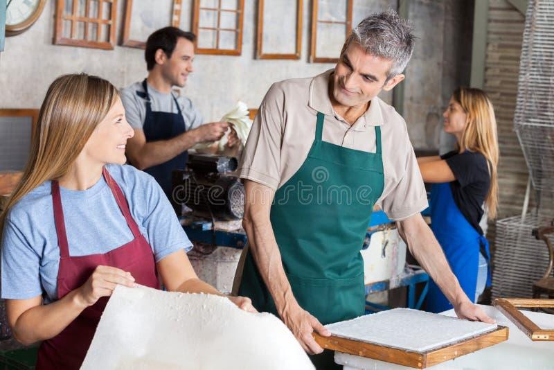 Работники делая бумаги пока смотрящ один другого стоковое изображение rf