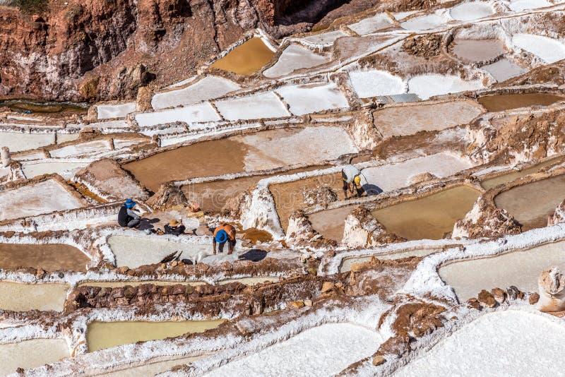 Работники делая их тяжелую работу на солевых рудниках и тазах, Salinera стоковое изображение