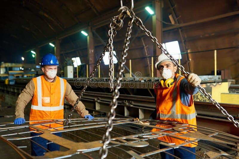 Работники завода по изготовлению стали используя поднимаясь луч стоковое изображение