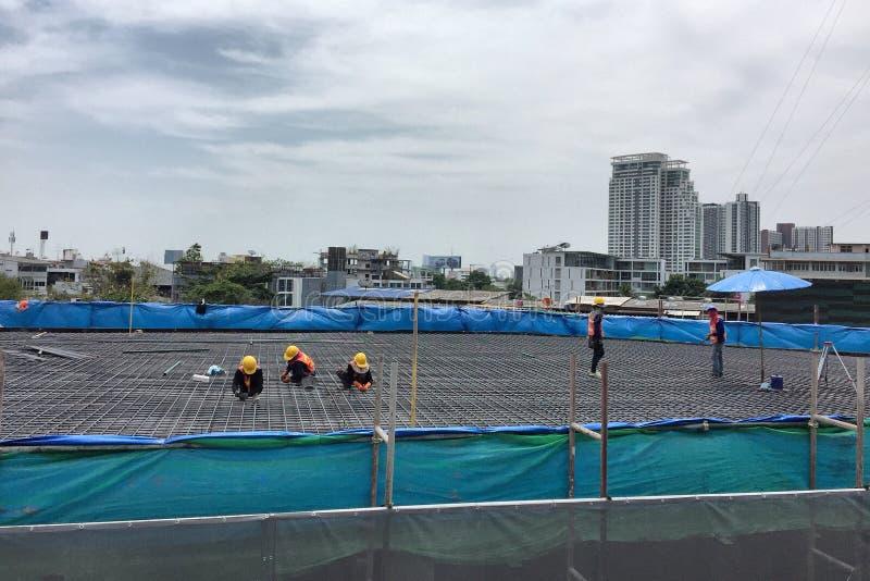 Работники изготовляя форма-опалубку тимберса столбца и бар подкрепления на строительной площадке стоковая фотография rf