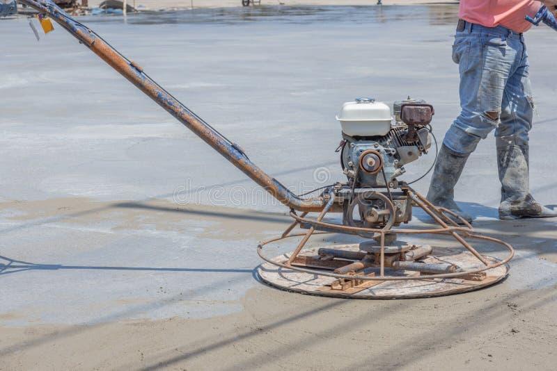 Работники используют конкретные полируя машины для цемента после лить готов-смешанный бетон стоковые изображения