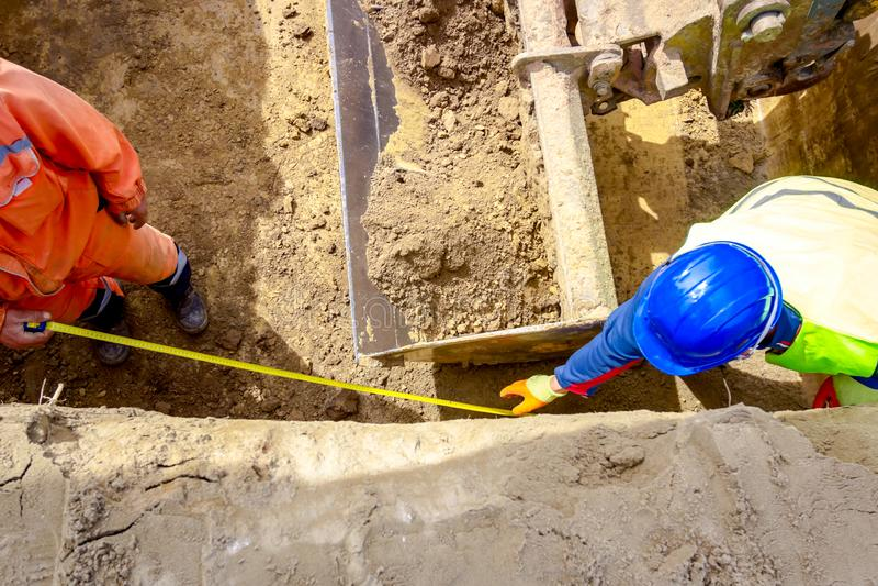 Работники используют ленту измерения земли на строительной площадке стоковое фото