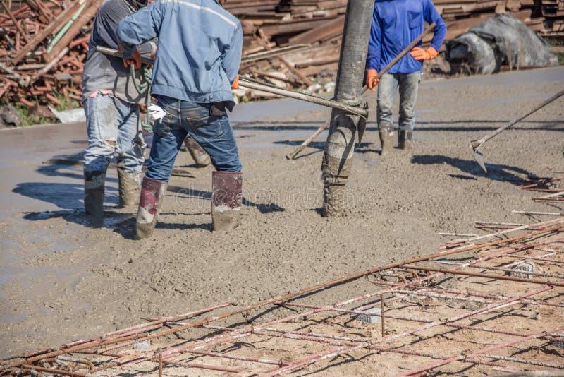 Работники используя деревянный шпатель для цемента после лить готов-смешанный бетон стоковые изображения rf