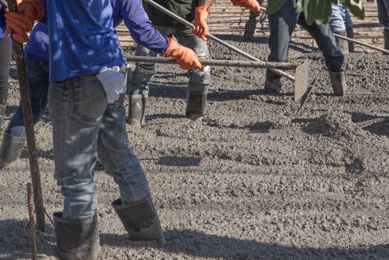 Работники используя деревянный шпатель для цемента после лить готов-смешанный бетон стоковые фотографии rf