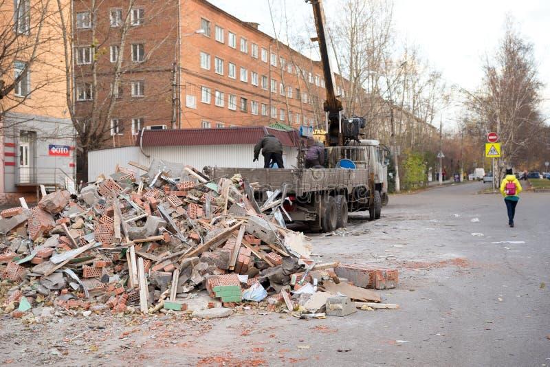 Работники коммунальных услуг положили отход конструкции от подрывания старых стойлов в тележку с краном в переулке стоковое изображение rf