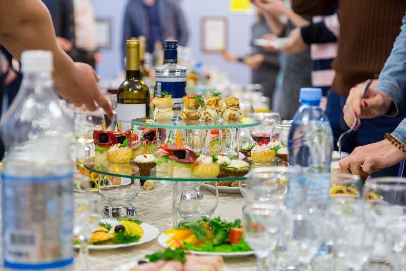 Работники компании на банкете Таблица с деликатесами, спиртом и закусками Торжественный прием стоковая фотография