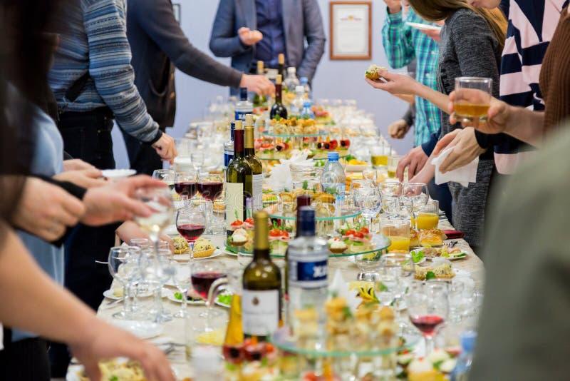 Работники компании на банкете Таблица с деликатесами, спиртом и закусками Торжественный прием стоковое фото