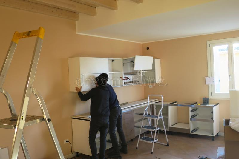 Работники людей пробуя установить кухню стоковое фото rf