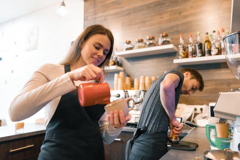 Работники молодой усмехаясь человек и женщина кофейни делая кофе с машиной, профессиональные baristas объединяются в команду дело стоковые изображения