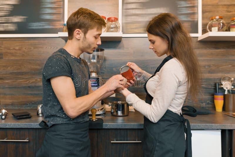 Работники молодой усмехаясь человек и женщина кофейни делая кофе с машиной, профессиональные baristas объединяются в команду дело стоковое фото