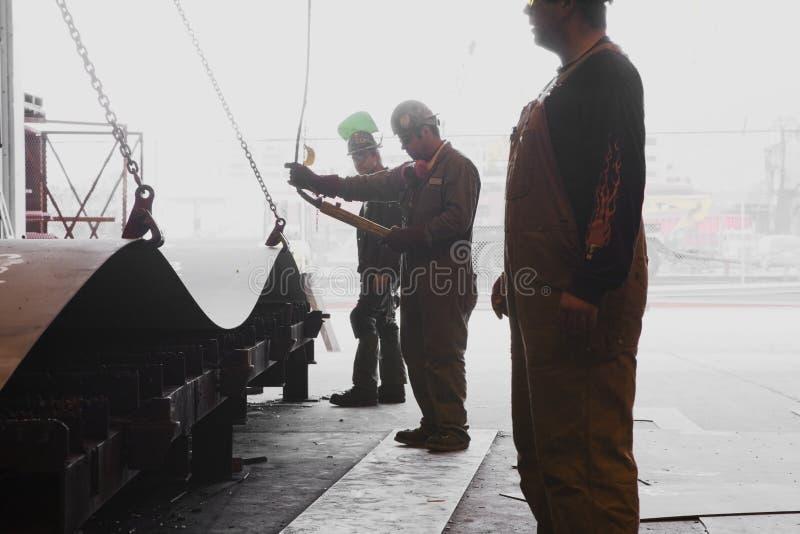 работники мужчины трудных шлемов coveralls стоковое изображение