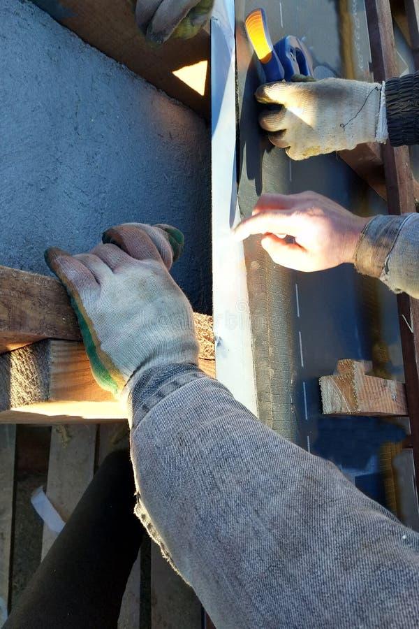 Работники на крыше дома устанавливают водоустойчивый фильм под крышу стоковые изображения