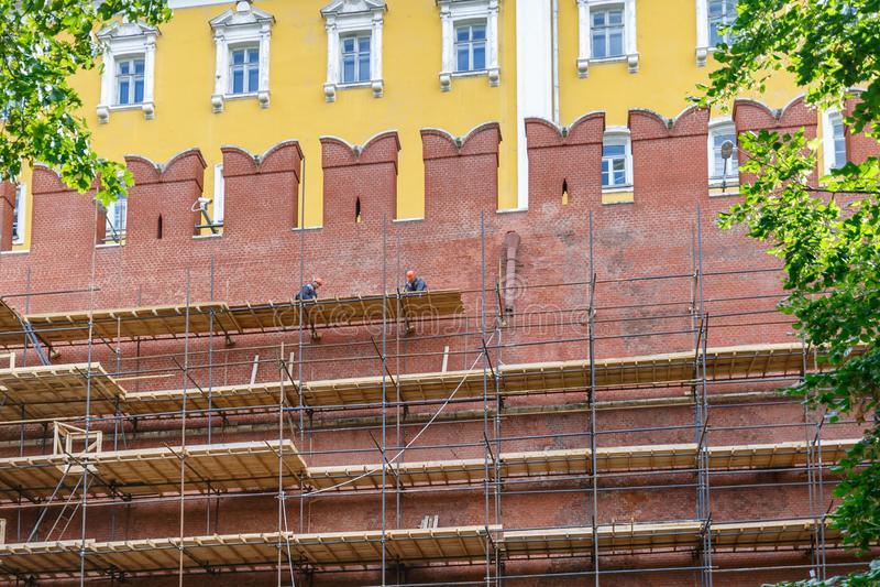 Работники на лесах приниманнсяые за реставрационные работы стены Кремля стоковые изображения rf