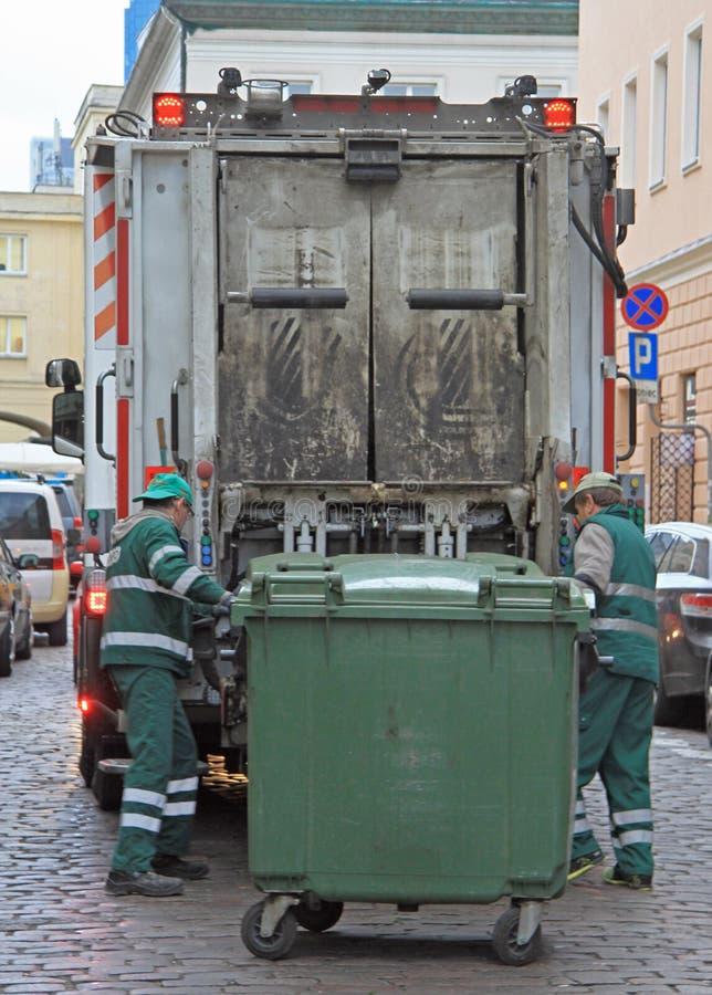 Работники обслуживания нагружают погань от мусорной корзины к мусоровозу стоковая фотография rf