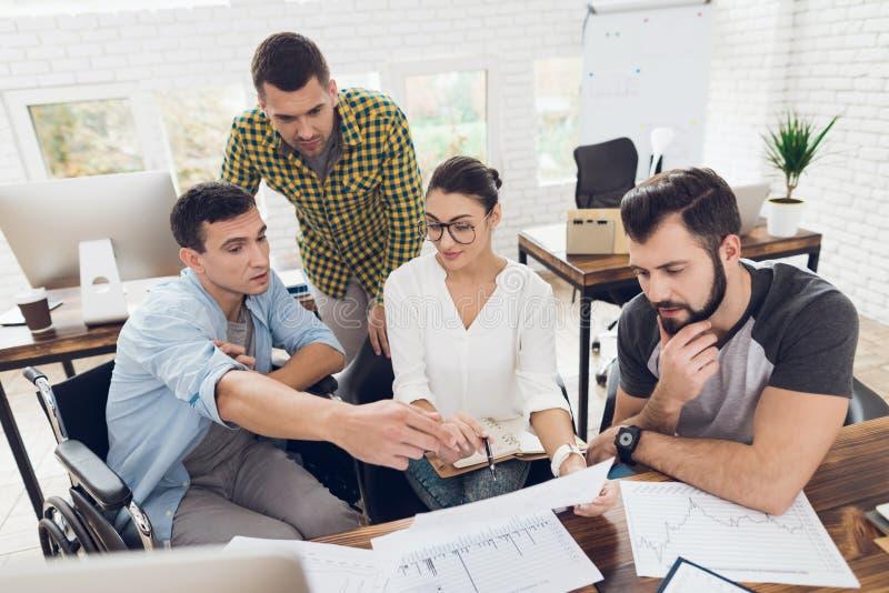 Работники офиса и персона в кресло-коляске обсуждают работать дела Они работают в ярком офисе стоковое фото