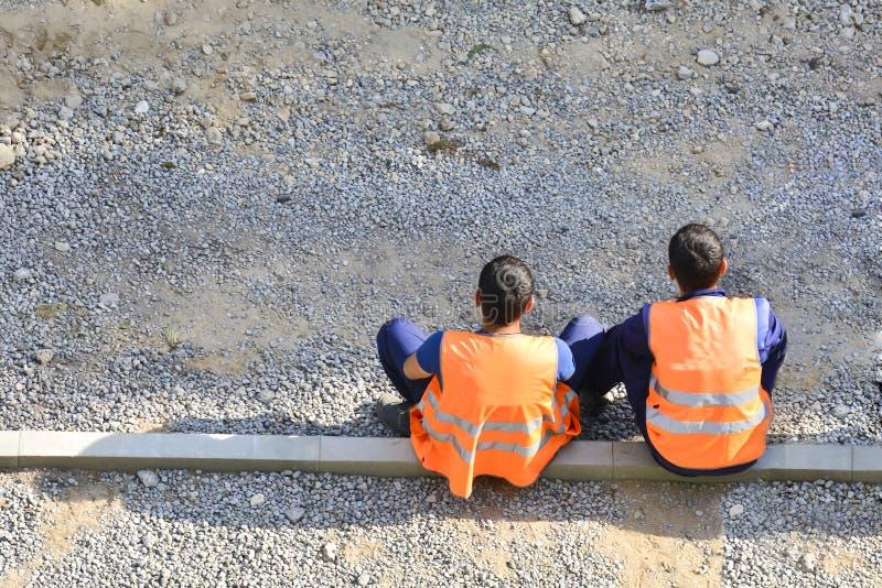 Работники переселенцев в желтых и оранжевых жилетах отдыхая дорогой Они сидят на боковых линиях Отремонтируйте дорогу r стоковые изображения