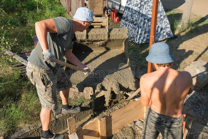 Работники полили бетон в деревянную форма-опалубку стоковые фото