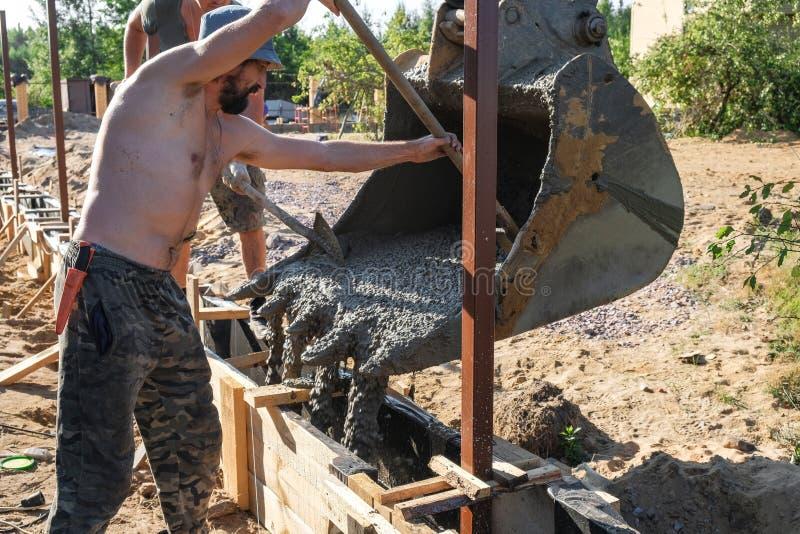 Работники полили бетон в деревянную форма-опалубку стоковые фотографии rf