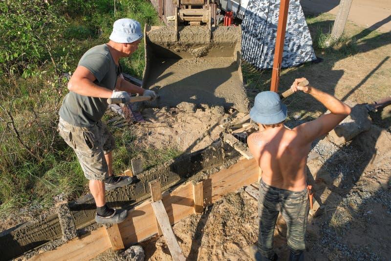 Работники полили бетон в деревянную форма-опалубку стоковое изображение