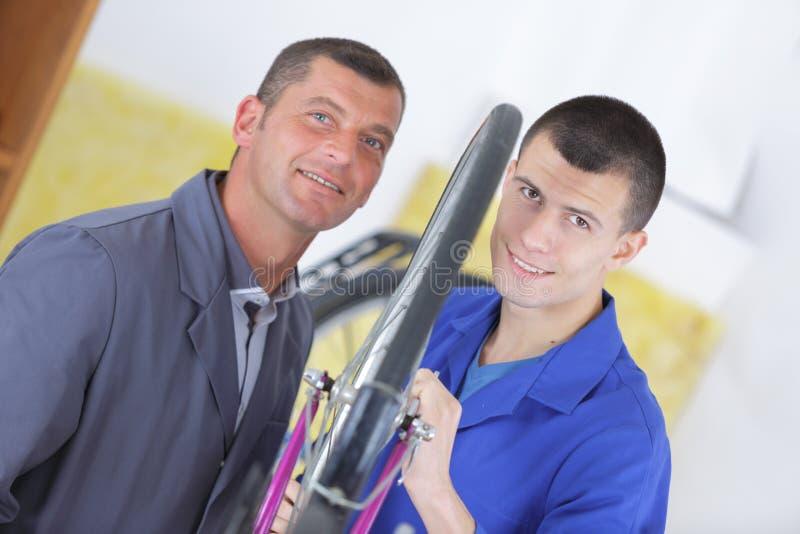 Работники портрета 2 мужские с велосипедом стоковое изображение
