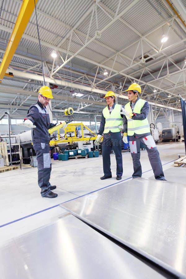 Работники приближают к алюминиевым заготовкам стоковые изображения