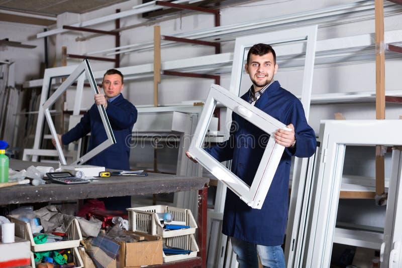 Работники проверяют продукцию обрабатывающей промышленности PVC стоковые фото