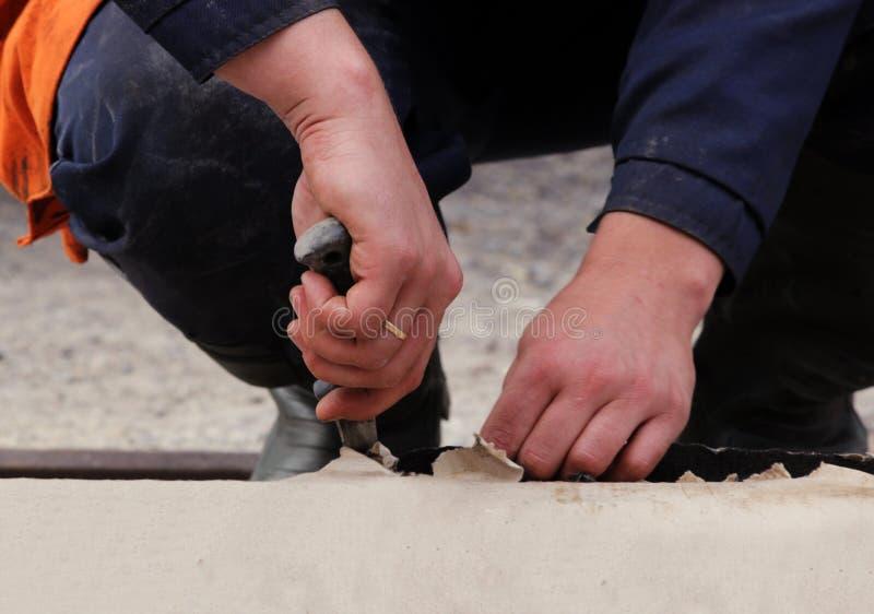 работники режут вне соединяют от крена материала толя для делая водостойким работы ремонта для того чтобы держать воду стоковая фотография