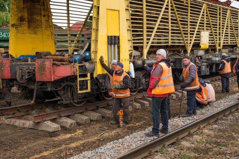 Работники ремонта модернизируют железнодорожный путь Irpin-Bucha на области Киева стоковая фотография