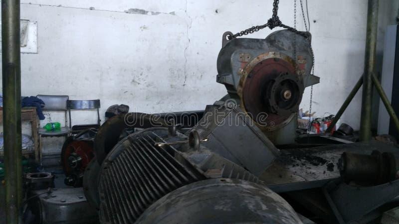 Работники ремонтируют промышленного машинного оборудования которое испытывает строгое повреждение Ремонт двигателей компрессора стоковое изображение rf