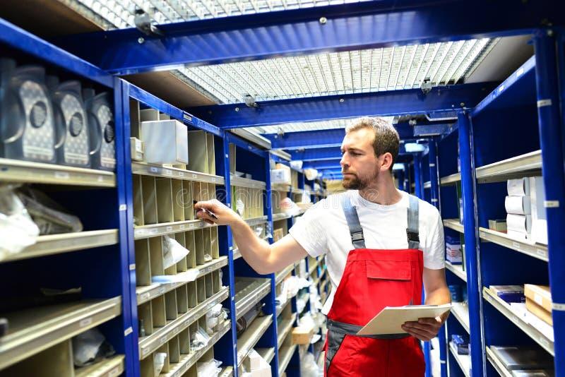 Работники ремонтной мастерской автомобиля в складе для запасных частей для r стоковые фотографии rf