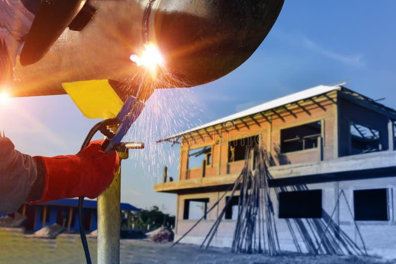 Работники сваривая конструкцию procecc дуговой сварки на предпосылке дома проекта деревни стоковая фотография