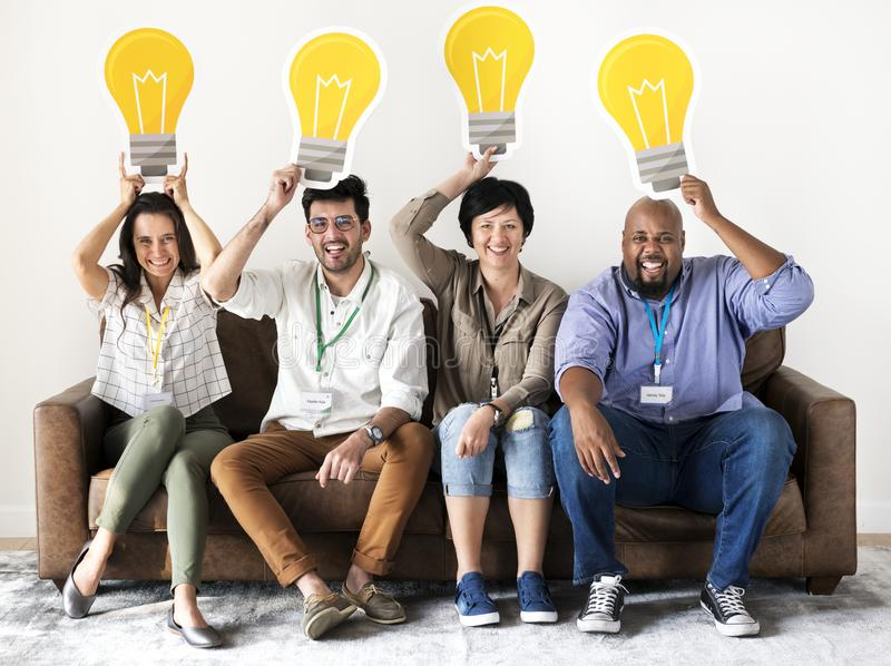 Работники сидя и держа значки лампочки стоковые изображения
