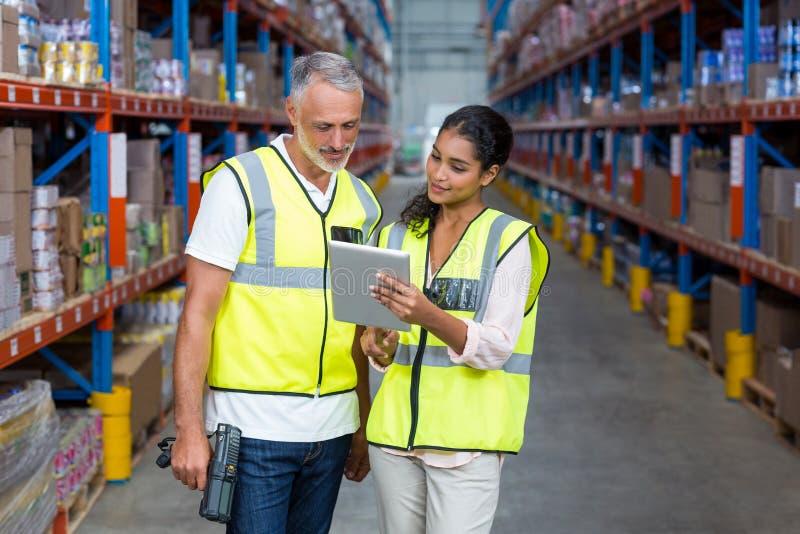Работники склада обсуждая с цифровой таблеткой стоковая фотография