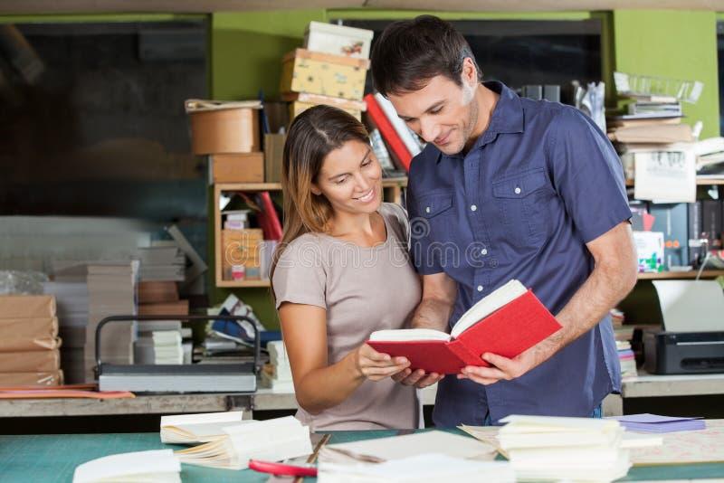 Работники смотря книгу в бумажной фабрике стоковые изображения