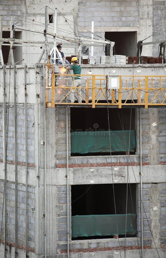 работники строительного подъемника стоковые фото