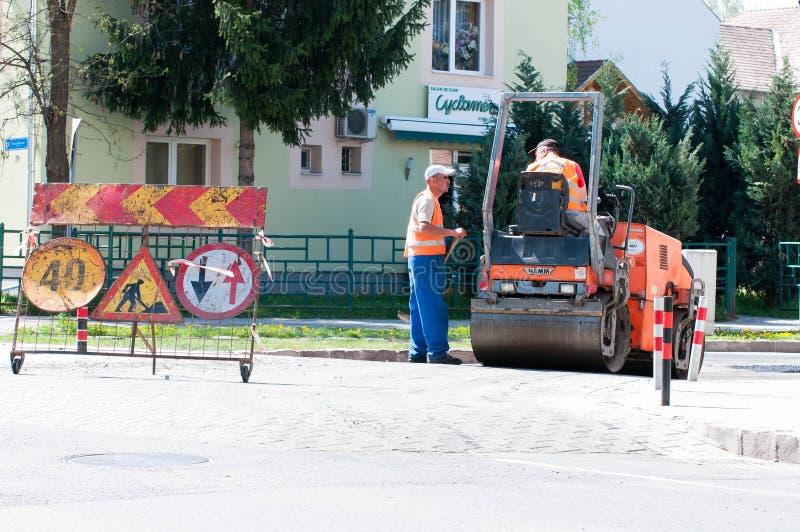 Работники строительства дорог ремонтируя дорогу стоковое фото