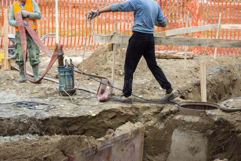 Работники с промышленной водяной помпой 2 погружающийся стоковые фотографии rf
