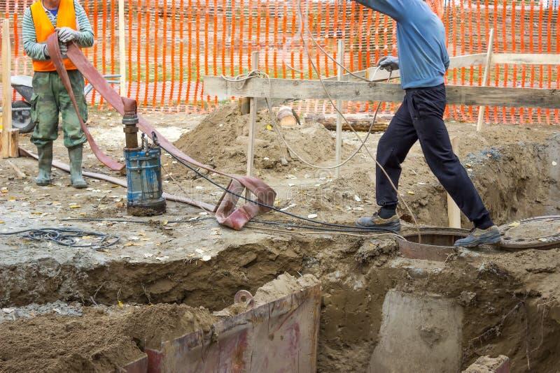 Работники с промышленной водяной помпой погружающийся стоковое фото rf