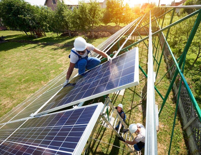 Работники управляют панелями солнечных батарей установки на крыше ` s дома стоковая фотография rf