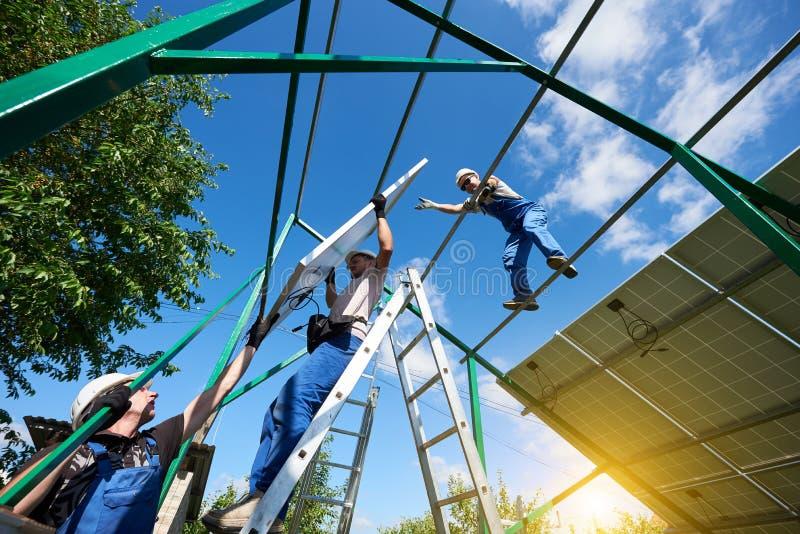 Работники управляют устанавливающ панели солнечных батарей на крышу стоковое изображение