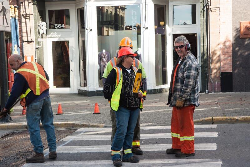 Работники улицы конструкции говорят о прогрессе в работе стоковое фото