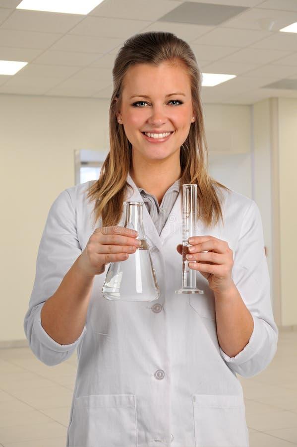Работник лаборатории держа стеклоизделие стоковое изображение