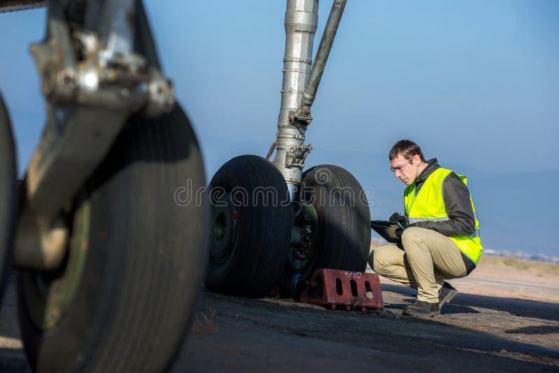 Работник авиапорта проверяя шасси стоковое изображение